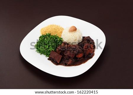 Brazilian Feijoada dish on brown background. - stock photo