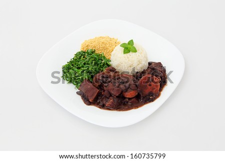 Brazilian Feijoada on a plate for lunch or dinner. Dish on a white background. - stock photo