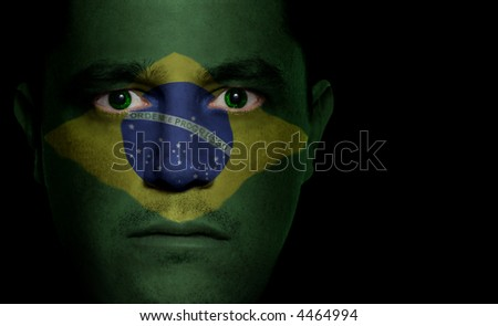 Brazilian flag painted/projected onto a man's face.