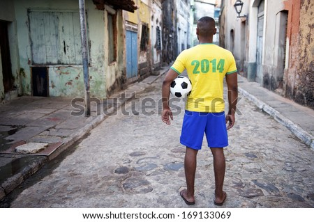 Brazilian football player in 2014 shirt stands holding a soccer ball on an old favela street in rustic village - stock photo