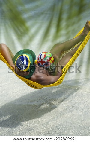 Brazilian football player relaxing in beach hammock with international team flag soccer ball - stock photo
