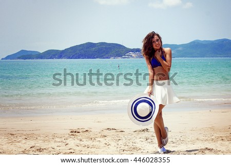 Brazilian girl dancing in white skirt and hat on the beach