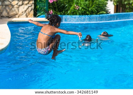 Brazilian girl jumping in tropical blue swimming pool in summer.  Active female child wearing colorful swimwear outside in pool area - stock photo