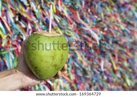 Brazilian hand holding coco gelado drinking coconut at wall of wish ribbons Bonfim Church in Salvador Bahia Brazil - stock photo