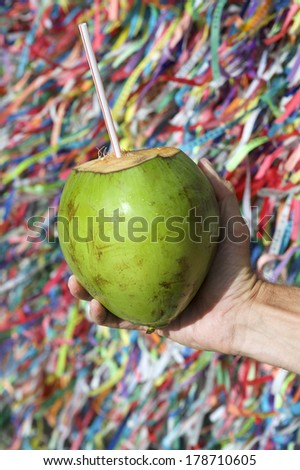 Brazilian hand holding coco verde gelado green drinking coconut at wall of wish ribbons in Salvador Bahia Brazil - stock photo