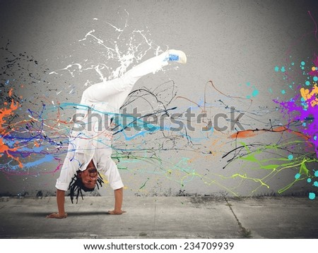 Brazilian man dressed in white dancing capoeira - stock photo