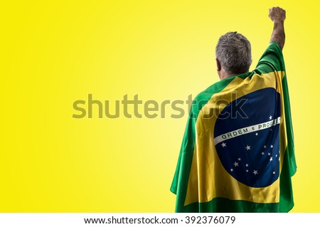 Brazilian man holding the flag of Brazil on yellow background - stock photo