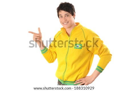 Brazilian man pointing in front. Attractive football fan with Brazil flag on his yellow sport blouse. Isolated on white. - stock photo
