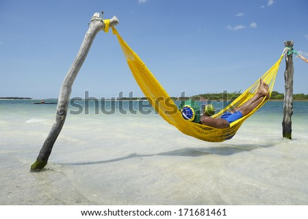 Brazilian man relaxing in beach hammock drinking fresh coconut water coco gelado - stock photo
