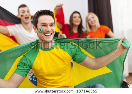 Brazilian man with friends from different country enjoying the soccer on TV - stock photo