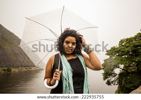 Brazilian model posing in the rain while holding a translucent umbrella - stock photo