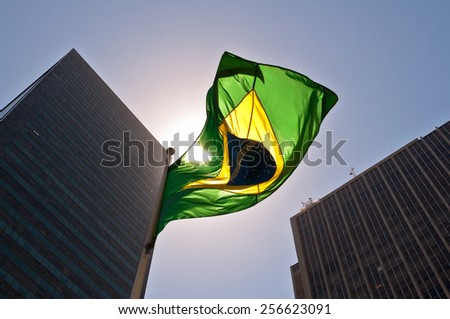 Brazilian National Flag against Skyscrapers by Sunset - stock photo