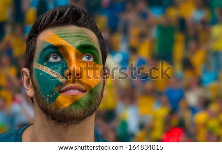 Brazilian painted the flag of Brazil on his face - stock photo