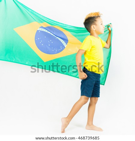 Brazilian patriot boy walking and holding Brazil flag. Football or soccer championship. Support fan. White background