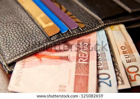 Brazilian real, euro and dollars in wallet - stock photo