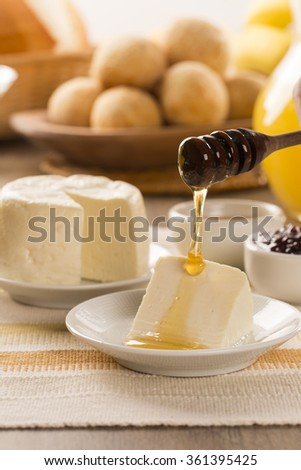 Brazilian sheep cheese. Bread, Fruits and different types of cheese in the background. - stock photo