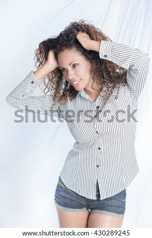 Brazilian smiling woman with curly hair and shorts