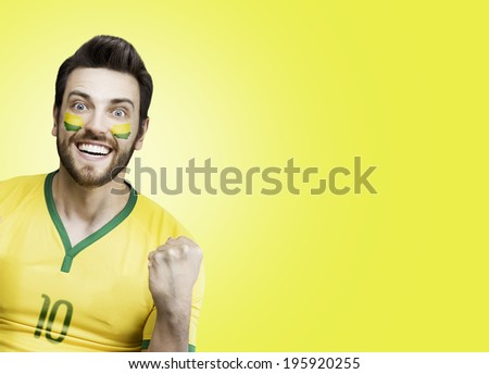 Brazilian soccer fan celebrates on yellow background - stock photo