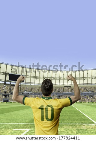 Brazilian soccer player celebrates with the fans on the stadium - stock photo