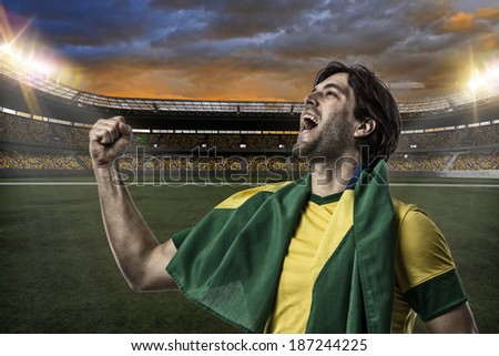 Brazilian soccer player, celebrating with the fans, on a Stadium. - stock photo