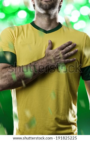 Brazilian soccer player, listening to the national anthem with his hand on his chest, on a green background. - stock photo
