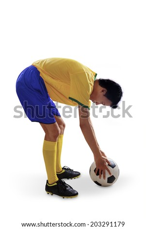 Brazilian soccer player put soccer ball on the floor. isolated on white - stock photo