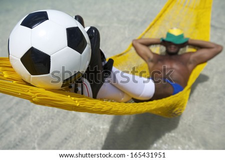 Brazilian soccer player relaxes in beach hammock with a football resting against his shoes - stock photo