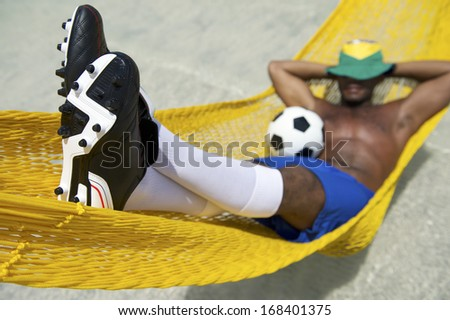 Brazilian soccer player relaxing in beach hammock with a football resting in his lap - stock photo