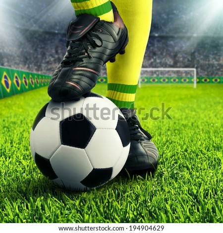 Brazilian soccer player's feet in casual pose in a football arena, with the crowd in the background - stock photo
