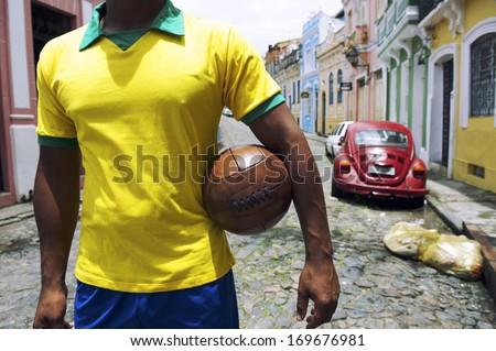 Brazilian soccer player standing on colonial Bahia street Pelourinho Salvador with vintage football - stock photo