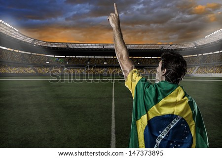 Brazilian soccer player with a Brazilian flag on his back, celebrating with the fans. - stock photo