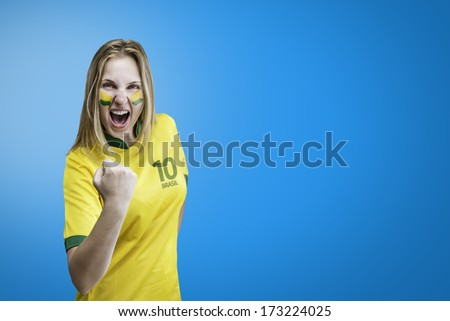 Brazilian woman celebrates on blue background with her face painted - stock photo