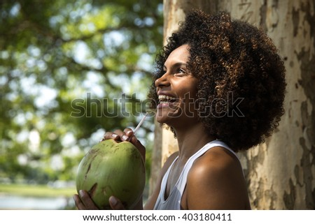 Brazilian woman drinking coconut water in the park - stock photo