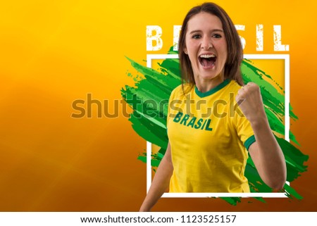 Brazilian woman fan, celebrating on a yellow background with copy space.