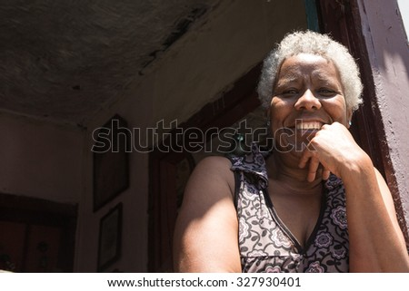 Brazilian woman smiling from the window - stock photo