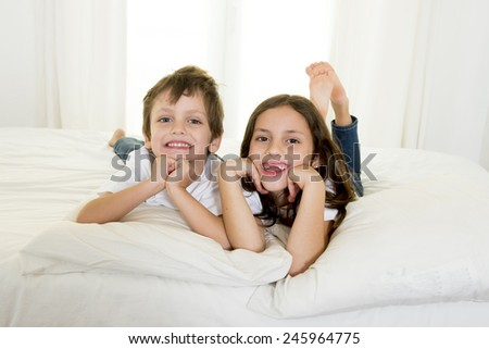 Brazilian 7 years old little girl playing on bed or couch together with her 4 years old small brother smiling happy in brotherhood and children lifestyle concept - stock photo