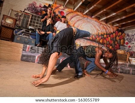 Brazillian capoeira martial artists tumbling and kicking - stock photo