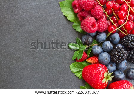 brder  of fresh  wild berries with green  leaves with copy space  on black stone background - stock photo