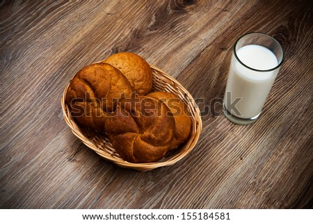 Bread and a glass of milk on the wooden table - stock photo