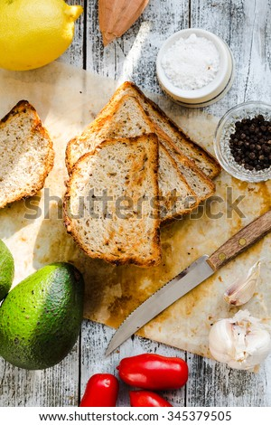 bread and a whole avocado with cherry tomatoes, pepper and garlic, a set of products to toast, snack,top view - stock photo