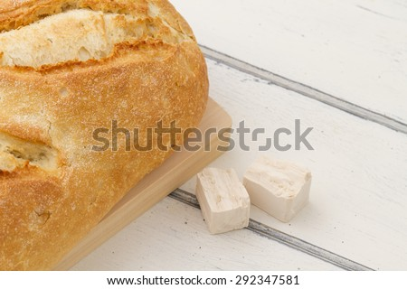 Bread and baker's yeast in a white wooden table