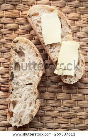 bread and butter are on the wicker napkin - stock photo