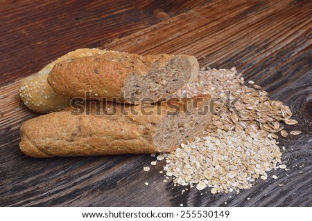 Bread and grains on wooden background - stock photo