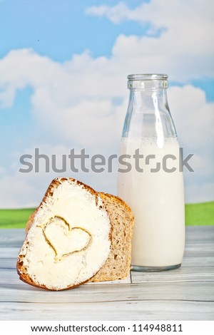 bread and milk in a bottle on a background of the sky - a picnic
