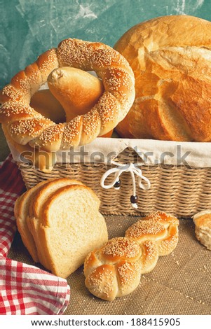 Bread and other baked goods in wicker basket on kitchen table