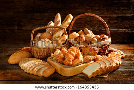 Bread and rolls in wicker basket on old wooden background.