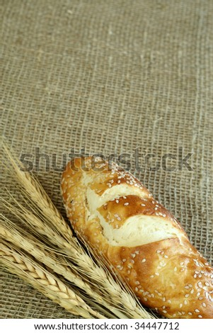 Bread and wheat ears on sacking.