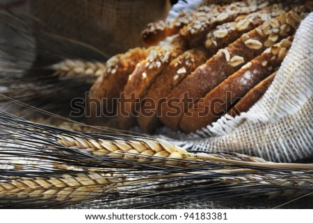 Bread and wheat ears on vintage wooden board