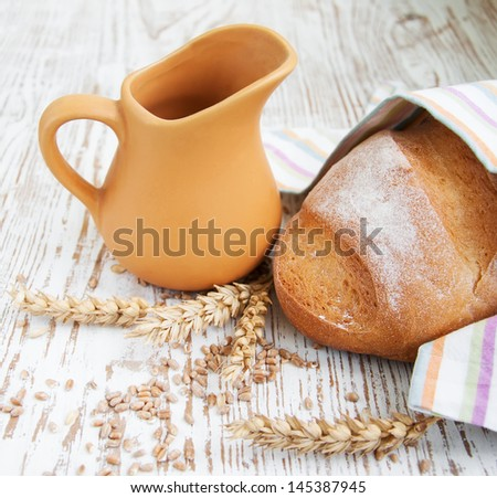 Bread and wheat on a wooden background - stock photo