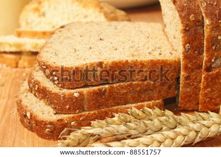 Bread and wheat on cutting board - stock photo